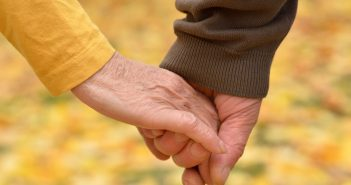 elderly couple holding hands image