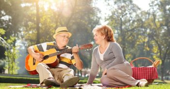 Man serenading his partner at the park