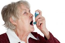 Senior woman spraying anti asthma on her mouth