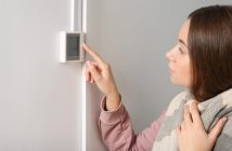 Woman adjusting thermostat