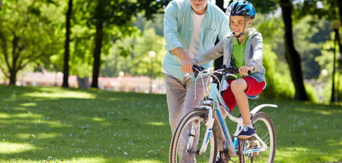 Happy grandfather teaching his grandson to bike