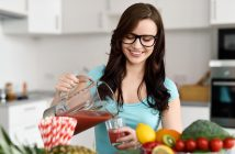 Young woman wearing glasses pouring vegetable